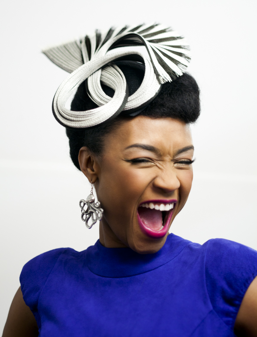 Editorial portrait of millenial woman wearing fashion hat while laughing.