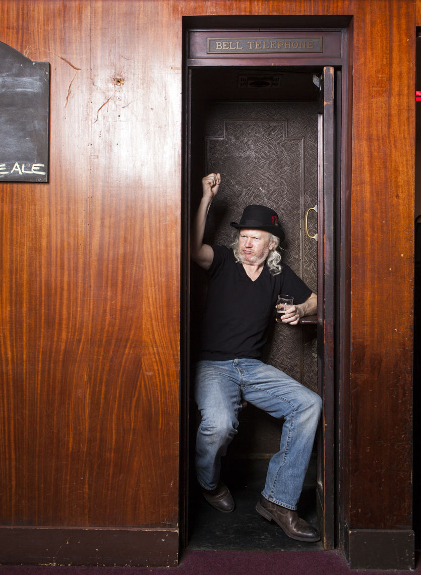 Editorial portrait of man sitting in phone booth while drinking a beer at a pub.