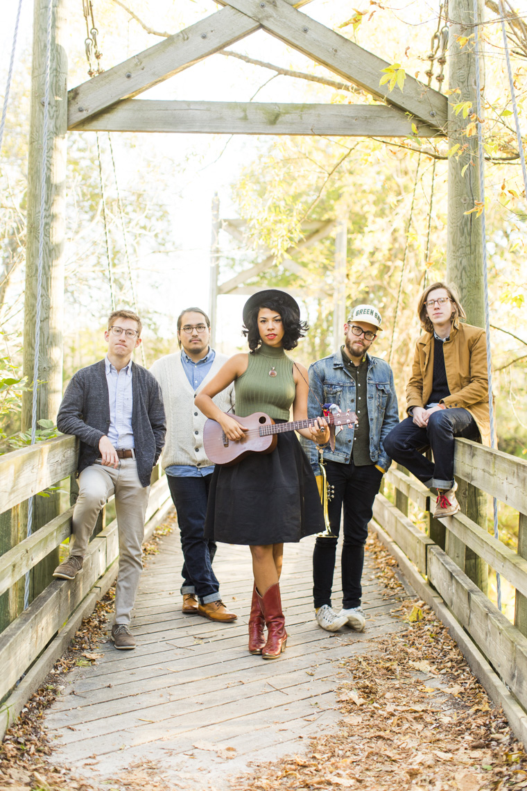 Editorial portrait of Midwestern rock band Phox standing on bridge with fall foliage.