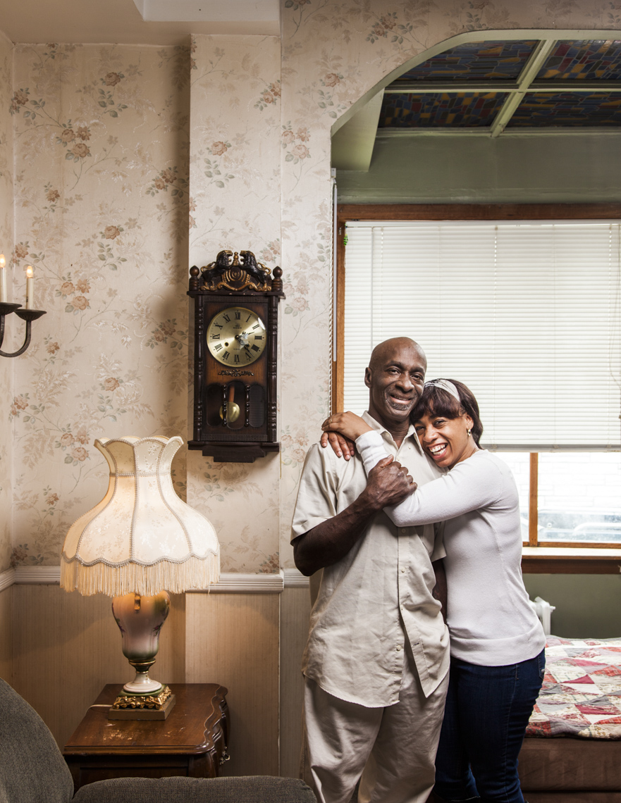 Portrait of happy African-American father and daughter in their living room