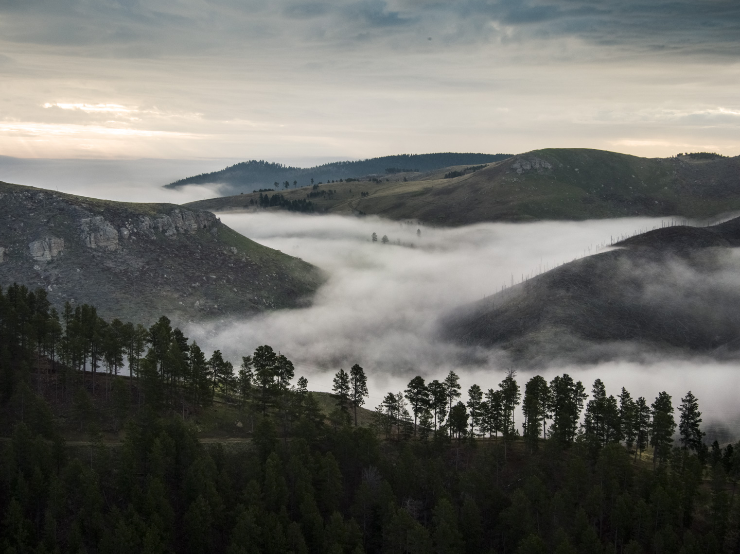 Fog rises through the mountains near Deadwood, South Dakota at sunrise