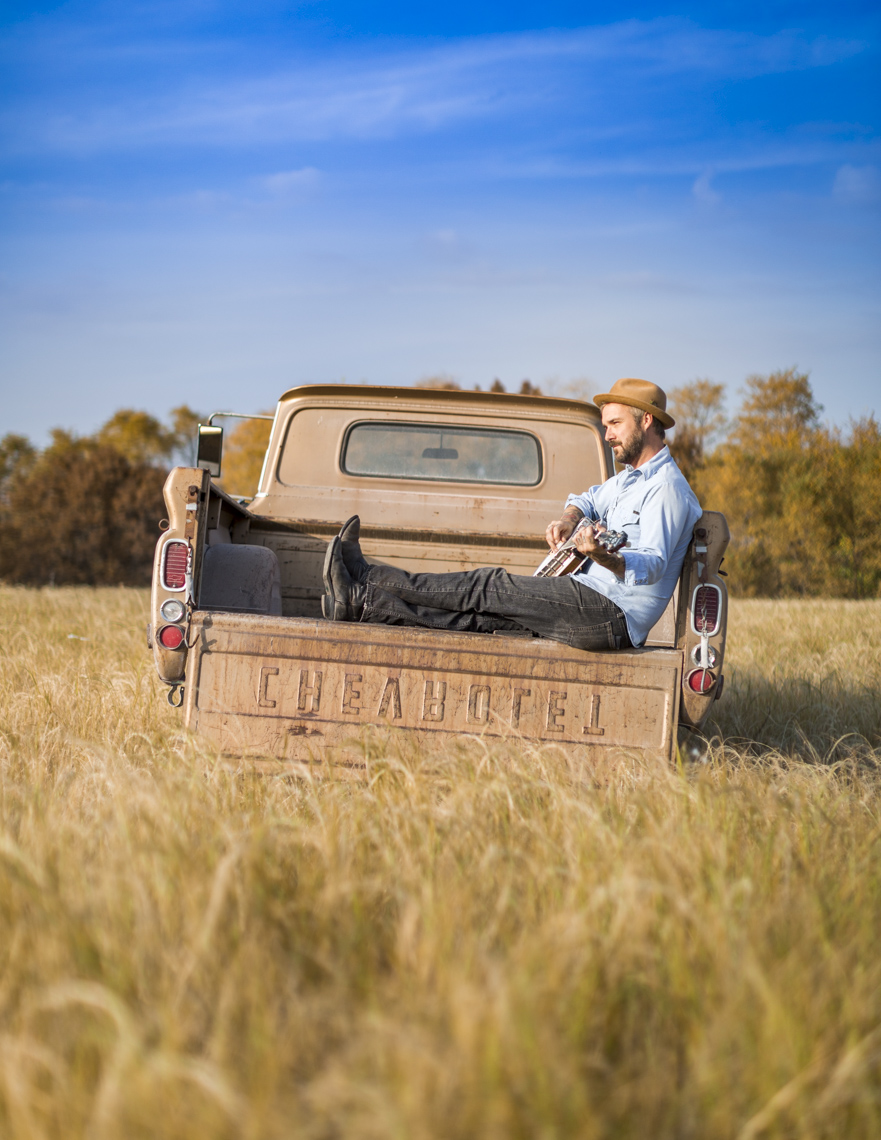 Portrait of Iowa musician William Elliott Whitmore in back of pickup truck.