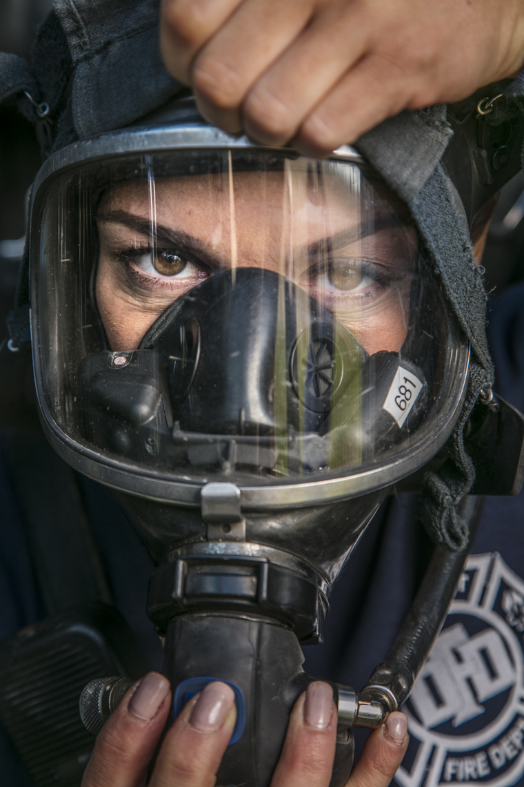 Portrait of female firefighter putting on her mask and gear.
