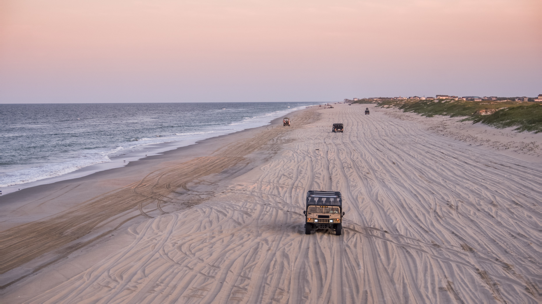 A Humvee driving down the beach at sunset for Wild Horse Adventure Tour in Corolla, North Carolina