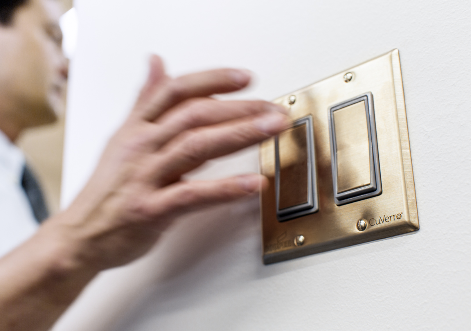 A man switches on a light switch, which is made from antibacterial metal