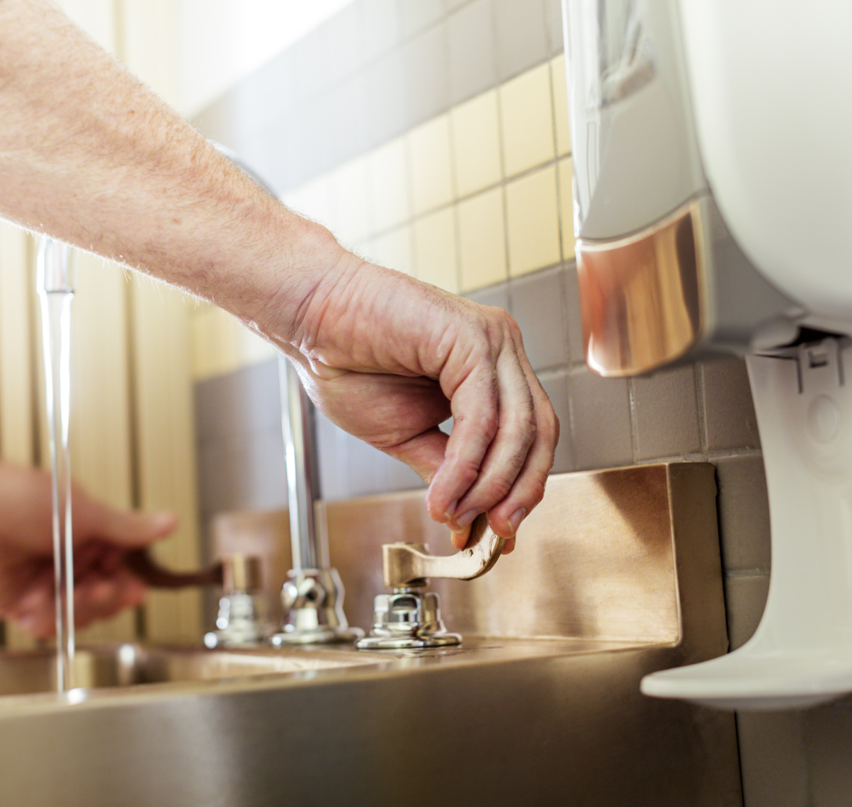 A man washes his hands at a hospital using a sink  made from antibacterial metal