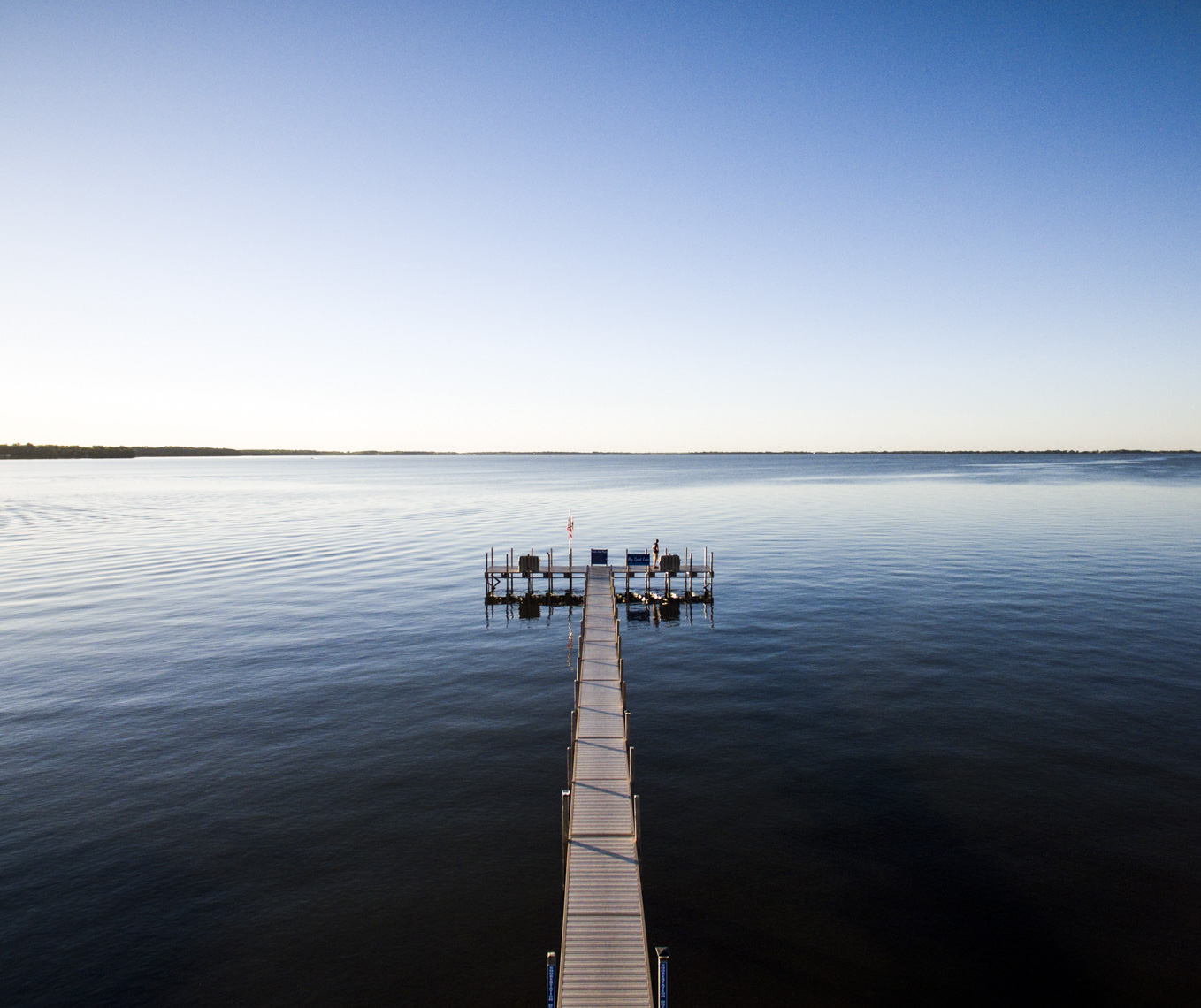Aerial view of boat dock at sunset on calm lake in Iowa.