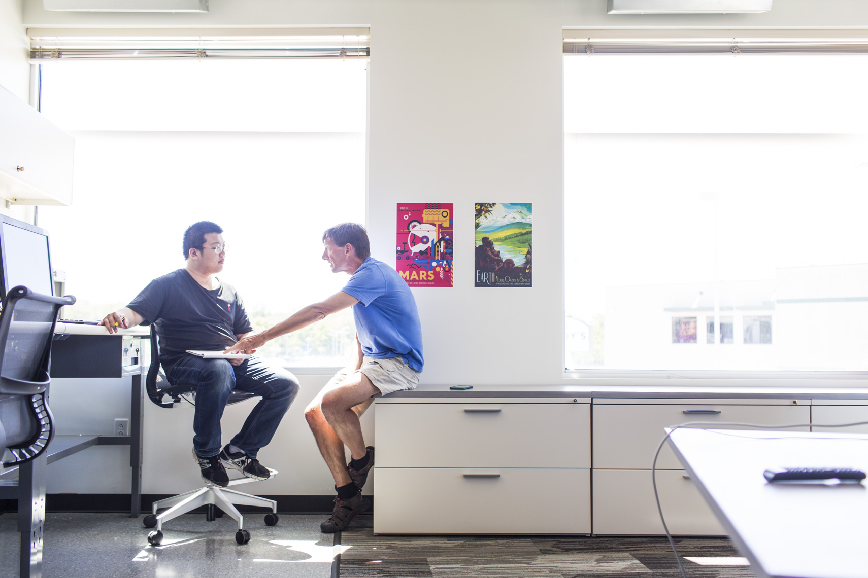 An older employee mentors a younger employee at a tech start-up company.