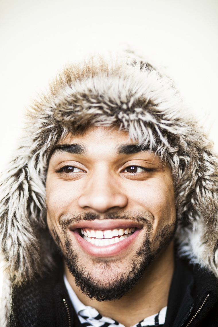 Portrait of smiling African American male student with furry hat